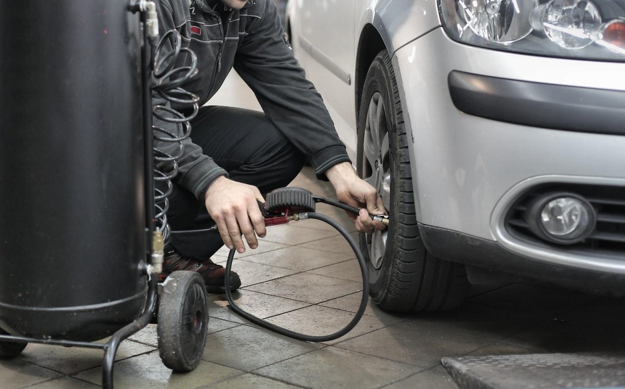 man pumping air into a tire