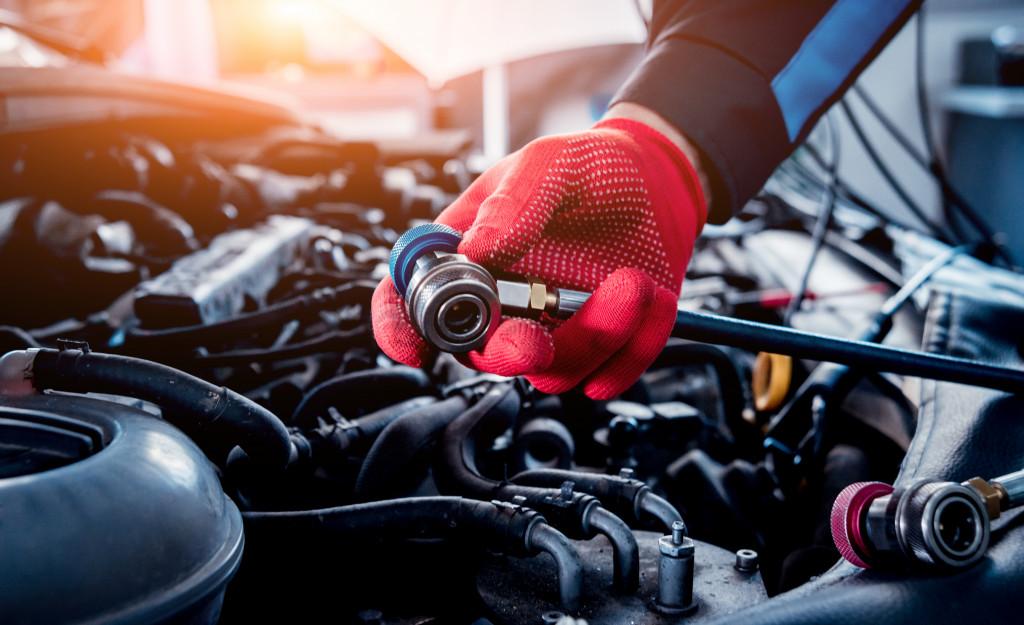man fixing car engine